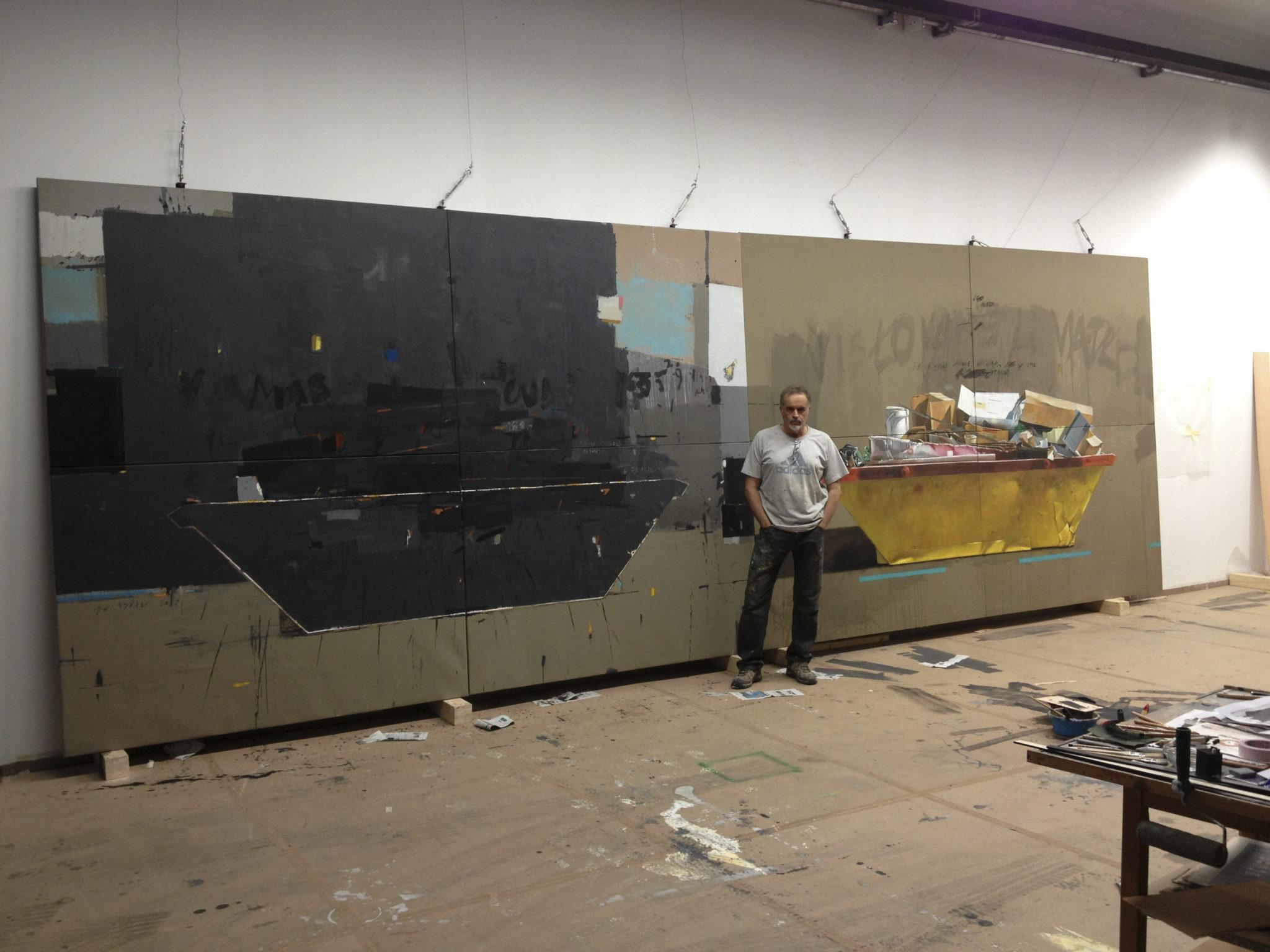 Fotografía del pintor Manuel Quintana Martelo, delante de una obra de grandes dimensiones que forma parte de la serie containers.